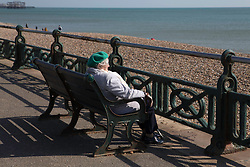 A woman looks out to sea on the seafront in Brighton, East Sussex, as the UK continues in lockdown to help curb the spread of Coronavirus.