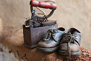 A pair of shoes and iron at the home of a Savings and Internal Lending Community (SILC) Paid Service Provider Philip Kogo with his children  in Eldoret, Kenya. His wife works as a teacher. They use the money they've been saving to add on to their home and pay for school fees. Sara A. Fajardo/Catholic Relief Services