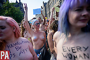 """'Free the Nipple' protestors march on the Royal Mile during the Edinburgh Fringe Festival. The women and men took their tops off to highlight issues around the objectification of women's bodies bearing slogans like """"Every Woman' and the particularly Scottish phrase 'The Revolution Will Be Taps Aff!'<br /> <br /> © Press Association<br /> All rights reserved"""