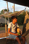 Young Surui workers return from working in their plantations to relax at sunset on their home verandah<br /><br />An Amazonian tribal chief Almir Narayamogo, leader of 1350 Surui Indians in Rondônia, near Cacaol, Brazil, with a $100,000 bounty on his head, is fighting for the survival of his people and their forest, and using the world's modern hi-tech tools; computers, smartphones, Google Earth and digital forestry surveillance. So far their fight has been very effective, leading to a most promising and novel result. In 2013, Almir Narayamogo, led his people to be the first and unique indigenous tribe in the world to manage their own REDD+ carbon project and sell carbon credits to the industrial world. By marketing the CO2 capacity of 250 000 hectares of their virgin forest, the forty year old Surui, has ensured the preservation, as well as a future of his community. <br /><br />In 2009, the four clans and 25 Surui villages voted in favour of a total moratorium on logging and the carbon credits project. <br /><br />They still face deforestation problems, such as illegal logging, and gold mining which causes pollution of their river systems