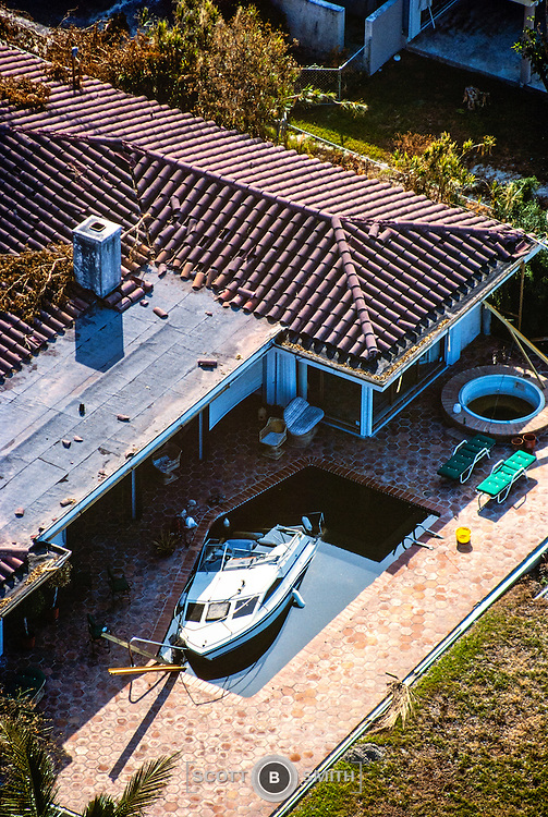 Aerial view of Hurricane Andrew damage shows boat blown into backyard pool