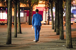 © Licensed to London News Pictures . 28/10/2018. Manchester, UK. A man wearing a blue suit and carrying a blonde wig , walks through trees in Piccadilly Gardens in Manchester City Centre . Revellers on a night out , many in fancy dress , on the weekend before Halloween . Photo credit: Joel Goodman/LNP