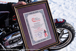 Vitaliy Timoshenko shows off his award certificate with his speed record achieved on his ice racer Harley-Davidson Sportster with sidecar during the Baikal Mile Ice Speed Festival. Maksimiha, Siberia, Russia. Saturday, February 29, 2020. Photography ©2020 Michael Lichter.