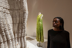 """© Licensed to London News Pictures. 21/10/2021. LONDON, UK. A model next to a sequin dress made from seaweed sequins by Philip Lim and Charlotte McCurdy. Preview of """"Waste Age: What can design do?"""", an exhibition at the Design Museum to see what the design industry can do to tackle its environmental consequences around the globe.  The exhibition coincides with the upcoming UN Climate Change Conference of the Parties (COP26) taking place in Glasgow.  Photo credit: Stephen Chung/LNP"""