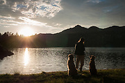A woman and her two dogs (golden retrievers) watch sunset at the edge of Upper Kinney Lake, Toiyabe National Forest, California