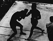 Les Riggins, right, landed a right to the head of George Davis as the two boxers were silhouetted in this unusual photo by Pete Liddell. Riggins, Seatlte, and Davis, Oakland Calif. fought to an eight-round draw. (The Seattle Times, 1971)