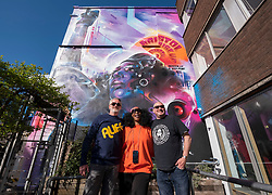 "© Licensed to London News Pictures; 02/04/2021; Bristol, UK. ALASDAIR DOGGART husband of JEN REID with artist MR CENZ, in front of ""United Souls United Goals"", an artwork by artist Mr Cenz, of a giant mural of Jen Reid, the woman who stood on the plinth of the statue of Edward Colston after it was torn down at a Black Lives Matter protest in Bristol in 2020 and of whom a statue was made and temporarily placed on the plinth. The mural is on the wall by The Canteen on Stokes Croft directly opposite Banksy's Mild Mild West mural, and replaces an earlier mural of Breakdancing Jesus. The mural is launched by The Bristol Eighteen and has the welcoming message ""Rise up Bristol, stand tall... Bristol's a city for all"" by poet Lawrence Hoo with Bristol's own street artist Inkie lending a hand to convey Lawrence Hoo's open-arms message of togetherness. The piece has been created to commemorate the Black Lives Matter protest in Bristol on June 7th 2020 and promote the ongoing global anti-racism movement. The Bristol Eighteen was formed, in the wake of the removal of Edward Colston's statue, to create a vehicle to raise funds for anti-racist educational organisations. Photo credit: Simon Chapman/LNP."