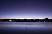 Boulder Reservoir glimmers at dusk below the silhouette of the Front Range outside Boulder, Colorado. The water of the reservoir, largely supplied by extensive tunnels and pipelines from the Western slopes of the Rocky Mountains, helps sustain human settlement along the Front Range.
