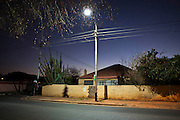 A street light shines over 9th Avenue at dusk, Sydenham, Johannesburg. South Africa.