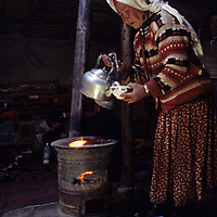 A nomadic Kyrgyz woman brews milk tea over a dung-burning stove in her summer hut in the Pamir Mountains of Xinjiang, China.