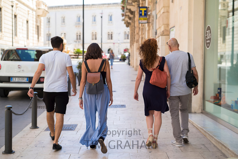 Stylish young people - couples - strolling in streets of Ortigia, Syracuse, Sicily