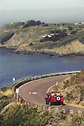 """Weekend getaway"" Red Jeep on northern California coast road in Sonoma County. Marin Headlands, Marin County."