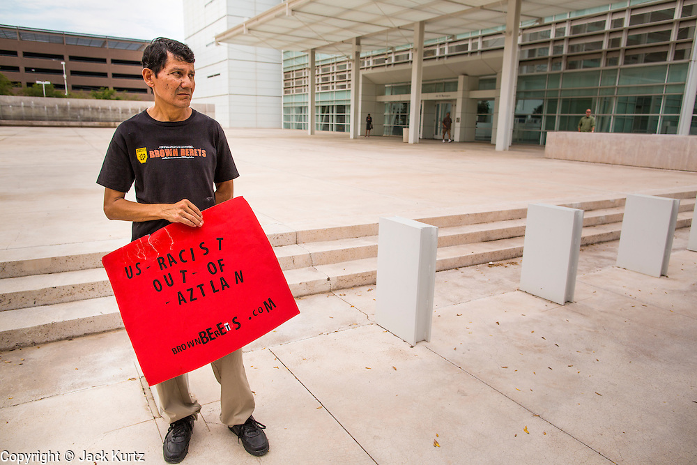 21 AUGUST 2012 - PHOENIX, AZ: A protester stands in front of the US federal courthouse in Phoenix. A handful of protesters waited outside the Sandra Day O'Connor Courthouse in Phoenix Wednesday while lawyers from the American Civil Liberties Union (ACLU) and Mexican American Legal Defense and Education Fund (MALDEF) sparred with lawyers from Maricopa County and the State of Arizona over the constitutionality of section 2B of SB 1070, Arizona's tough anti-immigrant law. Most of the law was struck down by the US Supreme Court in June, but the Justices let section 2B stand pending further review. The suit is being heard in District  Judge Susan Bolton's court. It was Judge Bolton who originally struck down SB 1070 in 2010. A ruling is expected later in the year.   PHOTO BY JACK KURTZ