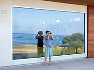 Boy with binoculars at beach house.