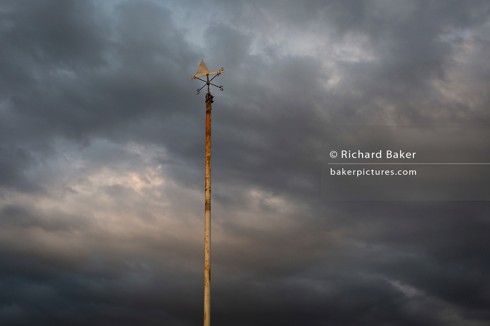 The points of a compass perches on top of a rusting post overlooking approaching storm clouds over the North Sea, on 13th July 2017, at Bridlington, East Riding, England.