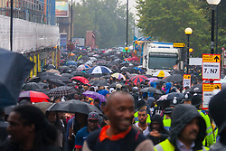 London, August 25th 2014. In spite of pouring rain, thousands of people enjoy the fun and vibrance of West London's Notting Hill Carnival procession.