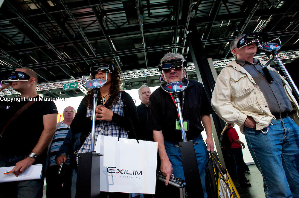 Visitors looking at 3D images  through 3D glasses at Photokina digital imaging trade show in Cologne Germany