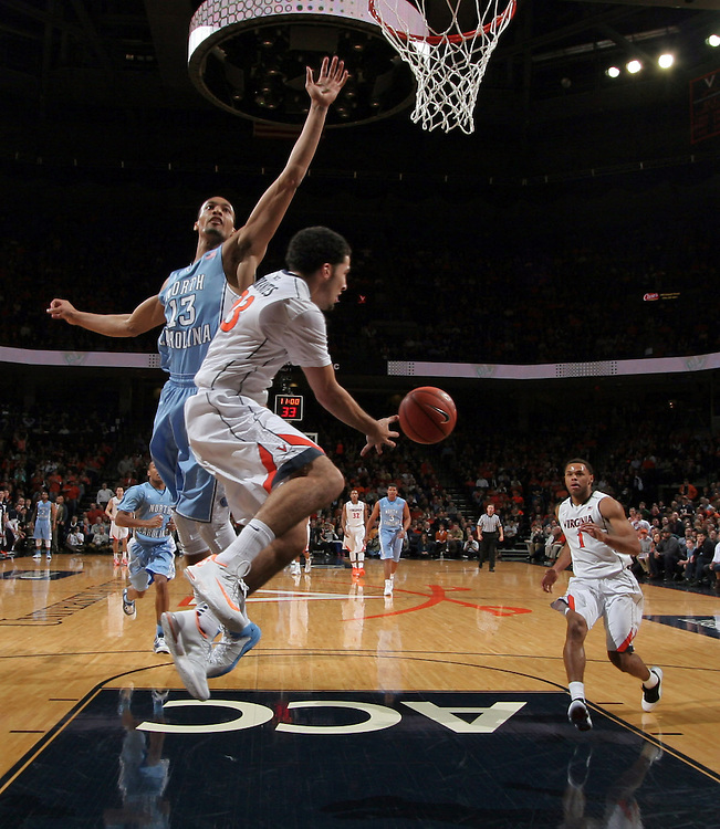 Virginia guard London Perrantes (23) passes the ball back to Virginia guard Justin Anderson (1) as he prepares to dunk the ball during an NCAA basketball game against Virginia Monday Jan. 20, 2014 in Charlottesville, VA. Virginia defeated North Carolina 76-61.