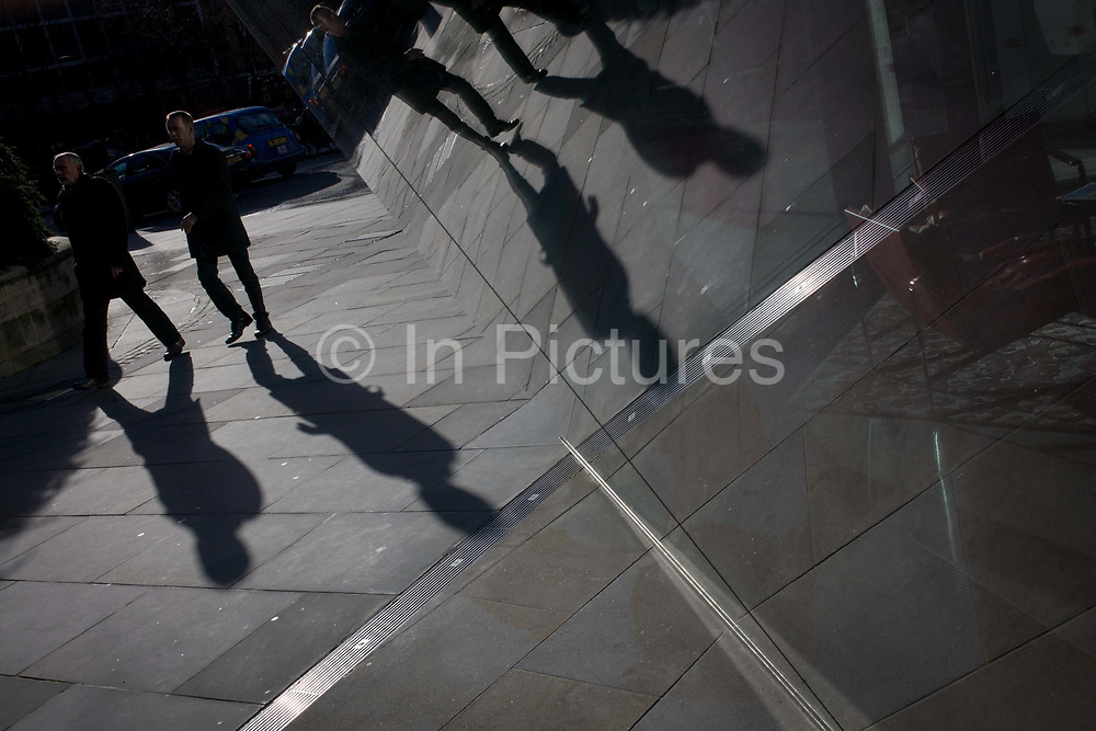 Angled passer-by reflections in sheet glass of City office entrance. The forms of two Londoners and their shadows pass near the windows of a corporate office foyer whose red seat is seen on the right. The view is angled to let the straight lines become diagonals that cross the photo, in the heart of the capital's financial centre, founded by the Romans in 43AD.