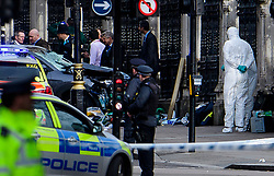 © Licensed to London News Pictures. 22/03/2017. London, UK. Police forensics examine a damaged car (grey, pictured left) involved in the incident, at the scene of suspected terrorist attack near Houses of Parliament in Westminster, London. Photo credit: Ben Cawthra/LNP