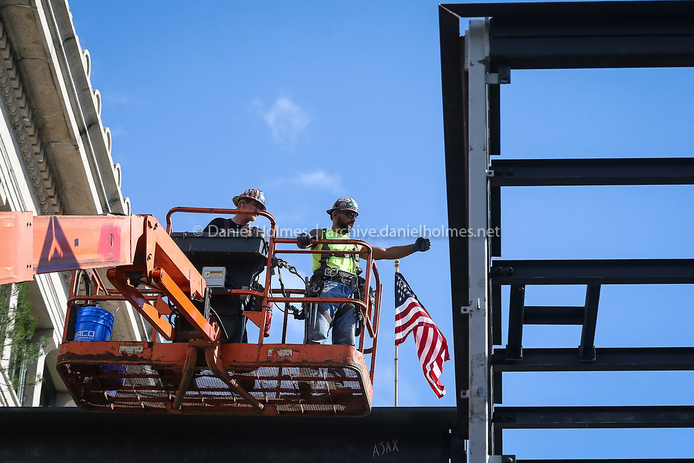 (10/4/16, FRANKLIN, MA) Joe Acquisto, right, and Sean Martin, of Ajax Construction, finish installing the topping beam during the topping off ceremony on the library renovation/expansion project at the Franklin Library on Tuesday. Daily News and Wicked Local Photo/Dan Holmes