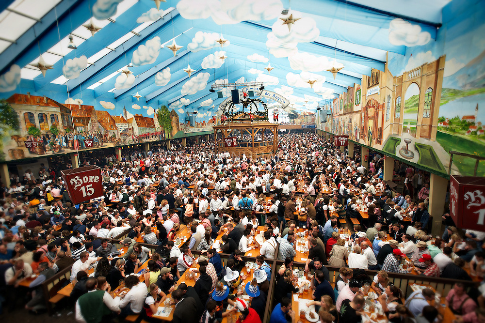 Thousands of people sitting in a large colorful tent eating and drinking at Oktoberfest in Munich, Germany