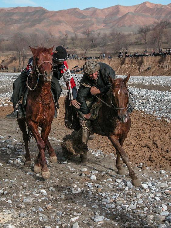 Image of Tajik horsemen fighting over the buz (a stuffed goat) while charging toward the finish at a buzkashi event in the village of Kostarosh, northwest Tajikistan