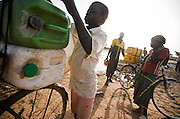 A boy ties plastic containers full of water to the back of his bike as he prepares to head home at the Dikunani dam in Savelugu, northern Ghana, on Friday March 9, 2007. The only of four water sources that has not completely dried out around Savelugu, the pond is used by hundreds of people daily who sometimes walk several kilometers to fetch water. Despite the presence of mesh filters available to people who come get water, cases of guinea worm in the area have gone up sharply in the recent months.