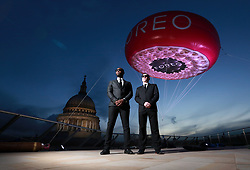 EDITORIAL USE ONLY<br /> Models Romeo Ugbene and Danny Coakley pose as the Men In Black infront of a 5 metre inflatable version of the new FOREO UFO, the world&Otilde;s first smart mask device appears at St Paul&Otilde;s in London to celebrate National Alien Day today.