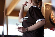 Ladies darts champion Anastasia Dobromyslova throws darts with her name stitched on her personalised shirt during tournament