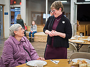"26 FEBRUARY 2020 - FARMINGTON, MINNESOTA: Pastor KAREN EVENSON, right, talks to a diner before the community dinner at Faith Church, a United Methodist Church in Farmington, MN, about 30 minutes south of the Twin Cities. She is the minister at the church. The dinner is sponsored by Loaves & Fishes, a Christian organization that provides food for community dinners and foodbanks. Farmington, with a population of 21,000, is a farming community that has become a Twin Cities suburb. The city lost its only grocery store, a Family Fresh Market, in December, 2019. The closing turned the town into a ""food desert."" In January, Faith Church started serving the weekly meals as a response to the store's closing. About 125 people per week attend the meal at the church, which is just a few blocks from the closed grocery store. The USDA defines food deserts as having at least 33% or 500 people of a census tract's population in an urban area living 1 mile from a large grocery store or supermarket. Grocery chains Hy-Vee and Aldi both own land in Farmington but they have not said when they plan to build or open stores in the town.      PHOTO BY JACK KURTZ"