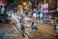 A woman driving an electric scooter stops along the roadside in Hanoi Vietnam, Southeast Asia