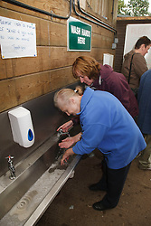 Woman with learning disability on trip to farm washing her hands