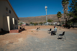 """A man waits to be seen at the TB """"ward,"""" a separate section at the De Doorns Clinic, a Western Cape government facility, in the Cape Winelands, where social-distancing rules are in effect, Wednesday May 6, 2020. The COVID-19 pandemic is a challenge, explains Abrey Arendse, Operational Manager here. Each morning, hundreds of patients line up outside the fenced clinic, according to social-distancing markers on the ground. She personally assesses everyone to see who needs to come inside the clinic right away, including the elderly, very sick, pregnant ladies and disabled people. Due to COVID-19, and space reasons, she can't let them all inside. There is also not enough PPE on hand for patients and no long-term stock for staff. Meanwhile, it's difficult to leave patients waiting in the elements outside. The sun is strong, and the winter rains are coming. PHOTO: EVA-LOTTA JANSSON"""