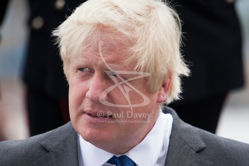 London, June 23rd 2014. Mayor Boris Johnson listens to speakers as members and veterans of the armed forces gather at City Hall for a flag raising ceremony to mark Armed Forces Day