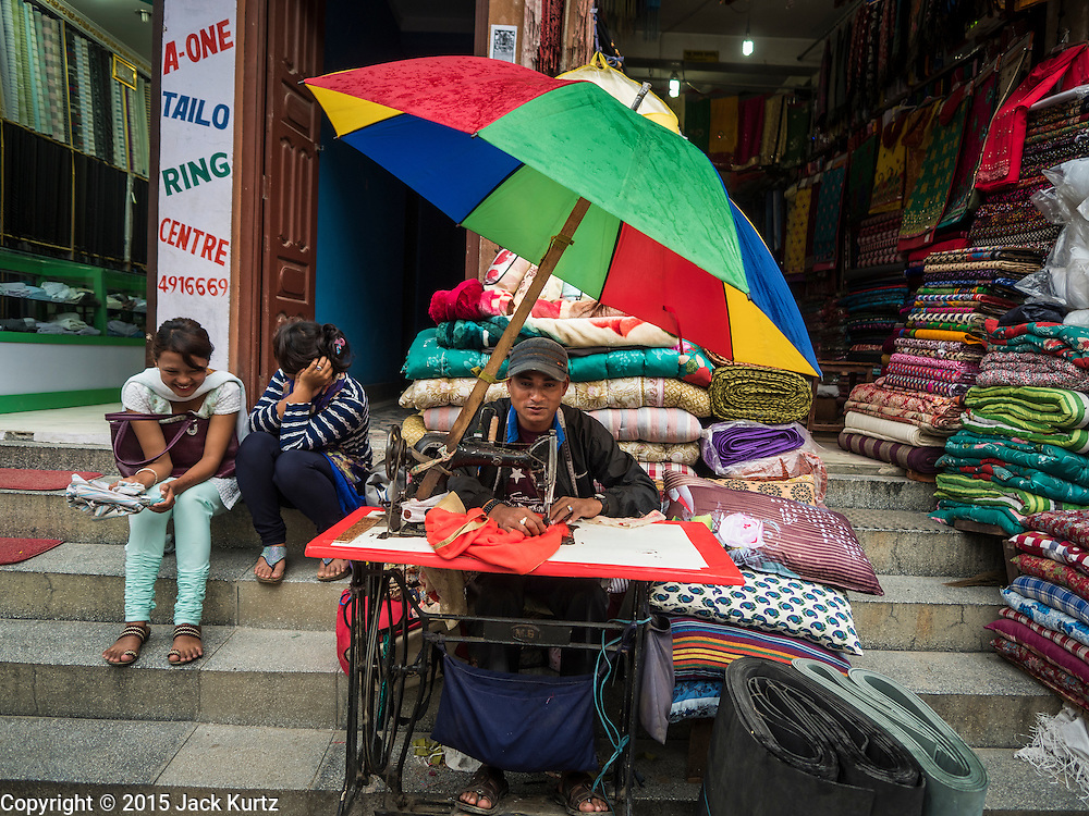 31 JULY 2015 - KATHMANDU, NEPAL: A tailor works in his street stall in Boudha, a Tibetan Buddhist enclave in Kathmandu. Tibetans started to move into the community in the late 1950s following the Chinese invasion of Tibet. The second largest Buddhist stupa in Asia is located in Boudha.   PHOTO BY JACK KURTZ