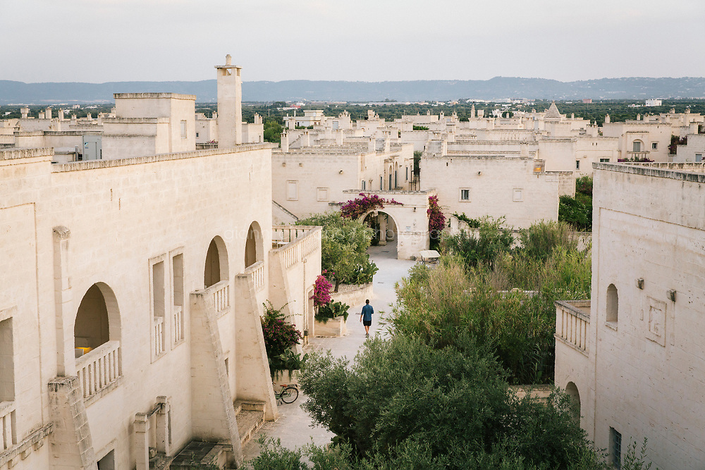"""FASANO, ITALY - 22 JULY 2018: A view of """"Il Borgo"""" (the village), reminiscent of a traditional Apulian village and the heart of the Borgo Egnazia property, a high-end resort in Puglia, is seen here in Fasano, Italy, on July 22nd 2018.<br /> <br /> Borgo Egnazia, modeled after a 15th century Apulian village, rolls out over 250 acres on a plot of land originally razed by Mussolini and intended as an air force base, ending nearing the Adriatic. Aldo Melpignano, the 40 years old owner, has pioneered a hospitality company that has managed to seize on the hype surrounding wellness and authentic experiences at once. His company, SD Hotels, turns Puglia's traditional farmhouses into resorts that focus on fitness (Apulian folk dance classes in 400 year old olive groves) and otherworldly spa treatments (one massage uses """"vibrational water"""") in addition to traditional Italian fare (milk serum, handmade orecchiette pasta, octopus in a broth of just-plucked tomatoes). <br /> <br /> Borgo Egnazia is the largest of his five properties, with three public pools, a village square out of central casting, and nearly 200 rooms.  Celebrities like Madonna have been won over by Borgo Egnazia's faux Medieval facades and farmhouse chic interiors, an effect best described as """"Game of Thrones"""" meets Restoration Hardware. Justin Timberlake and Jessica Biel got married here in 2012. SD Hotels, which last year saw revenues of $57 million, started with his family's summer home, Masseria San Domenico, a few miles down the road from Borgo Egnazia."""