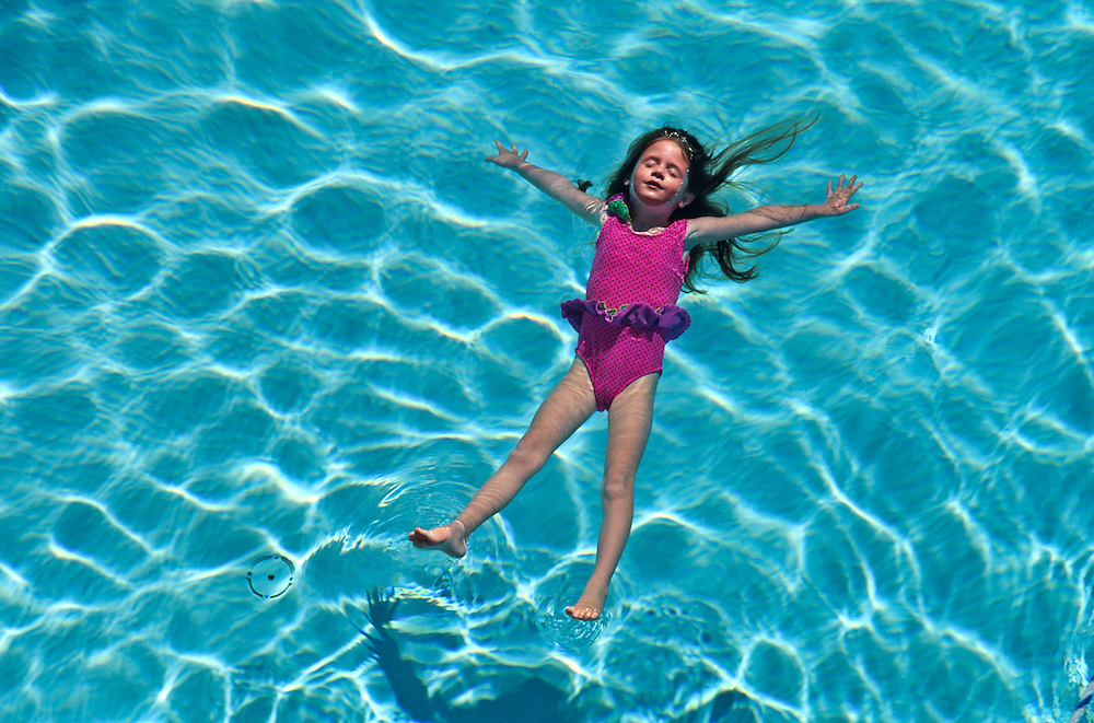 A young girl floating in a pool.