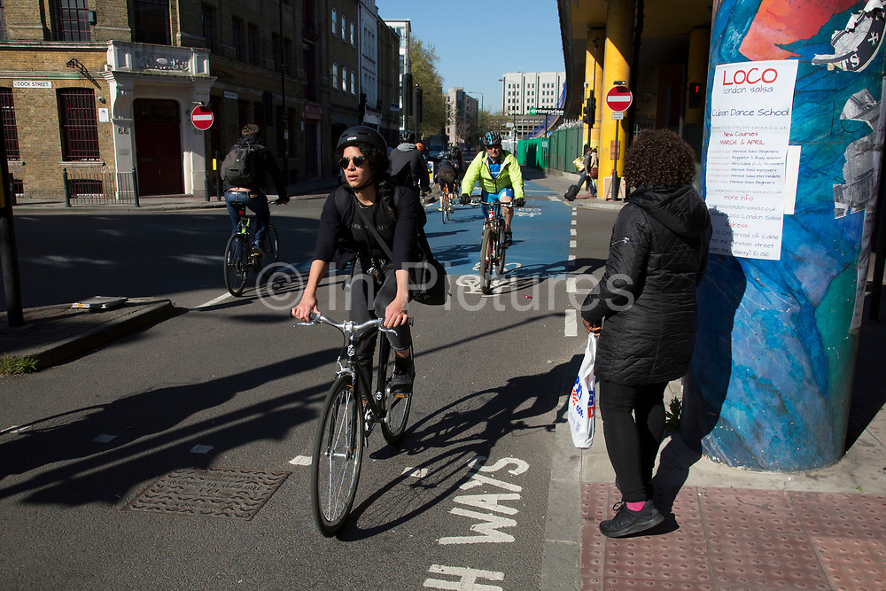 People and cyclists passing an advertising billboard on a street corner on Cable Street, London, UK.