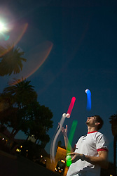 Stanford student Miguel Chavez juggles in the Stanford University Quad at dusk.