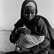 A young Somali refugee is seen waiting outside the registration centre with her new born baby at the IFO-1 camp in the Dadaab refugee camp in northeastern Kenya. Hundreds of thousands of refugees are fleeing lands in Somalia due to severe drought and arriving in what has become the world's largest refugee camp. Photo: Sanjit Das/Panos