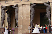 Saint Petersburg, Russia, June 2002..Bridal parties with the Atlas statues at the Hermitage, former home of the Tsars, and one of the world's great museums..