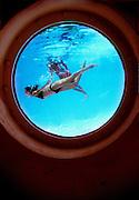 Seen through a porthole in the side of the swimming pool, two bikini-clad women swim like mermaids at Miami Beach's Art Deco, Nautical Moderne-style Albion Hotel.