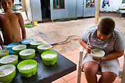 """Reinard (14 years old) is having breakfast before going to school nearby. In the camp, some volunteer prepares the breakfast for all the kids. The breakfast consists in the """"pap"""": ground maize mixed with milk."""