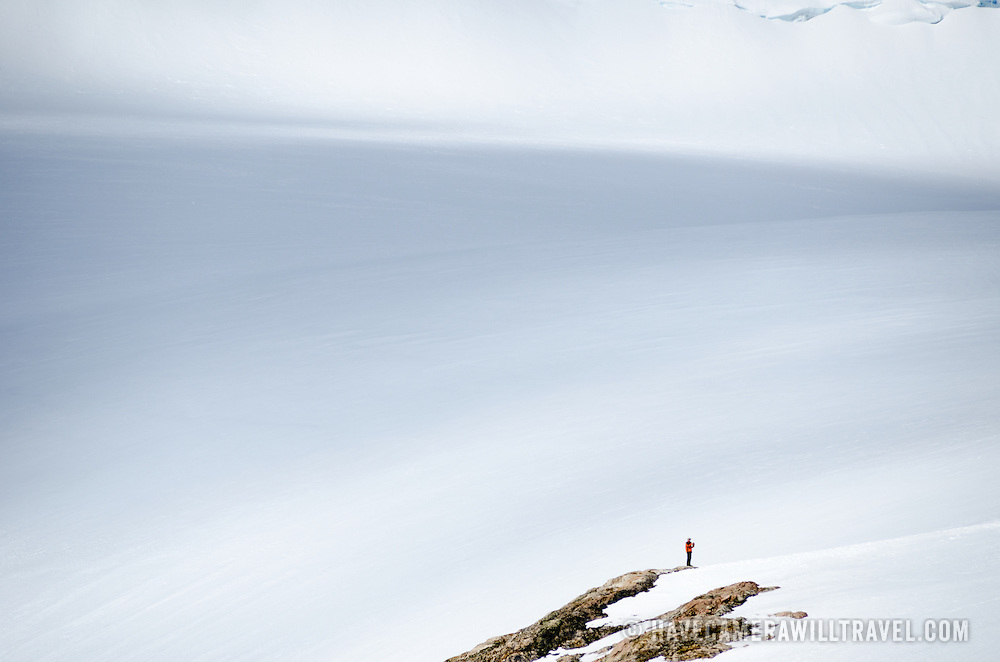 A man stands on a rocky outcrop overlooking an expanse of ice on the side of a mountain at Neko Harbour, Antarctica.