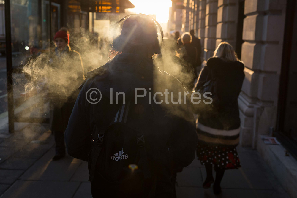 A man wearing headphones exhales a cloud of vape smoke in winter sunshine on Piccadilly, on 20th January 2020, in London, England.