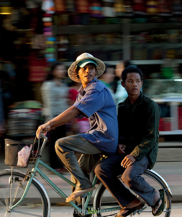 Young men cycle through the streets of Siem Reap, Cambodia