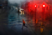 Boy crossing the road during a wet day in the Kings Cross area during the third lockdown of the Coronavirus pandemic, on 3rd March 2021, in London, United Kingdom.