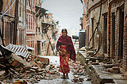 A woman walks through the rubble of homes destroyed during the 2015 Nepal earthquake.