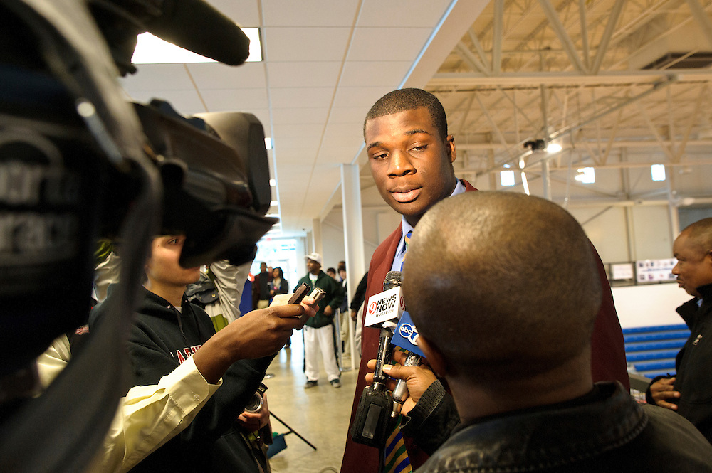 """Cyrus Kouandjio, one of the nation's top high school football players from DeMatha Catholic High School in Hyattesville, MD, talks to reporters after the 6'7"""" offensive tackle announced at the signing ceremony in the school's Convocation Center that he will be signing with Auburn, not Alabama where his older brother plays. He, however, did not sign his letter of intent. Three days later he announced he committed to play for the Crimson Tide."""